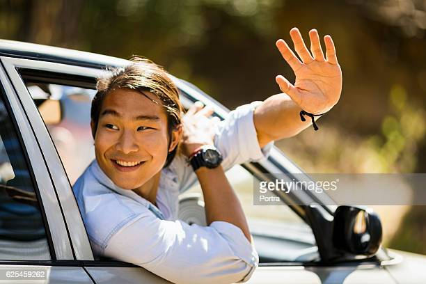 Smiling man waving hand from car window