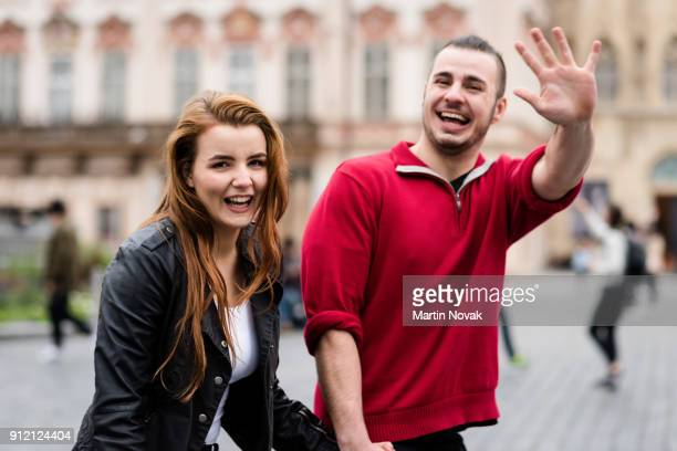 smiling man waving his hand at camera - waving stock pictures, royalty-free photos & images