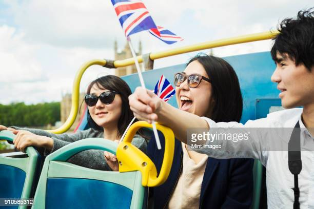 Smiling man waving Union Jack flag and two women with black hair sitting on the top of an open Double-Decker bus.
