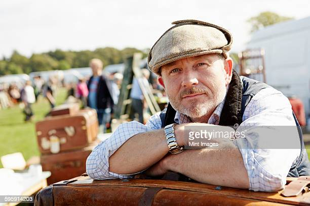smiling man wearing a flat cap at a flea market, a trader resting leaning on a pile of cases  - flat cap stock pictures, royalty-free photos & images