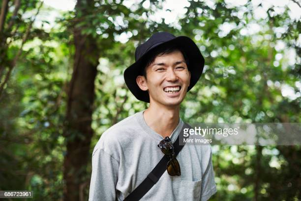 smiling man wearing a hat standing in a forest. - 大人のみ ストックフォトと画像