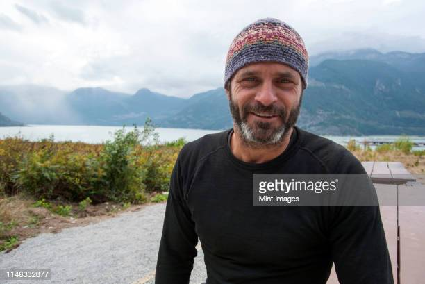 smiling man wearing beanie hat outdoors - gray hat stock pictures, royalty-free photos & images