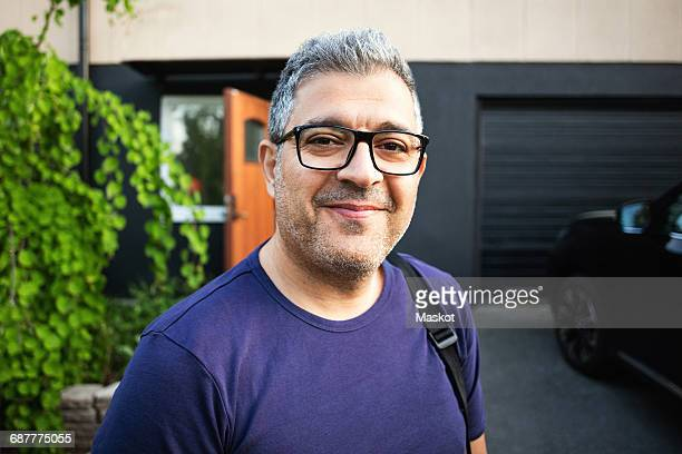 Smiling man wearing eyeglasses standing against house