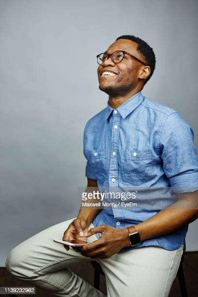 smiling man wearing eyeglasses using mobile phone while sitting against gray background - shirt stock pictures, royalty-free photos & images