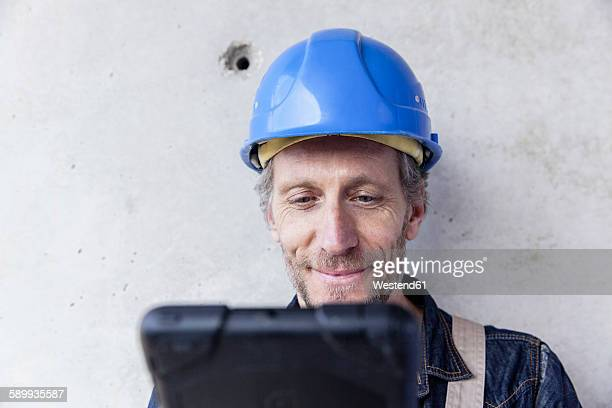 Smiling man wearing hard hat looking at digital tablet