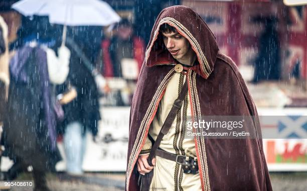 Smiling Man Wearing Hooded Cape During Rainfall