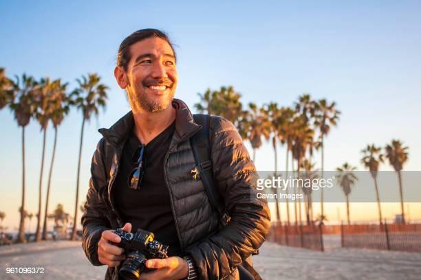 Smiling man wearing jacket while holding camera at beach