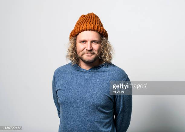 smiling man wearing knit hat on gray background - knit hat stock pictures, royalty-free photos & images