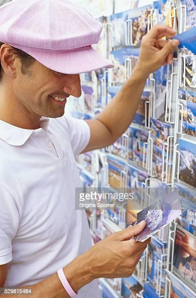 Smiling Man Wearing Pink Cap Choosing Postcards