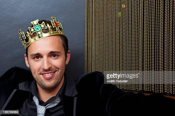 Smiling man wearing plastic crown