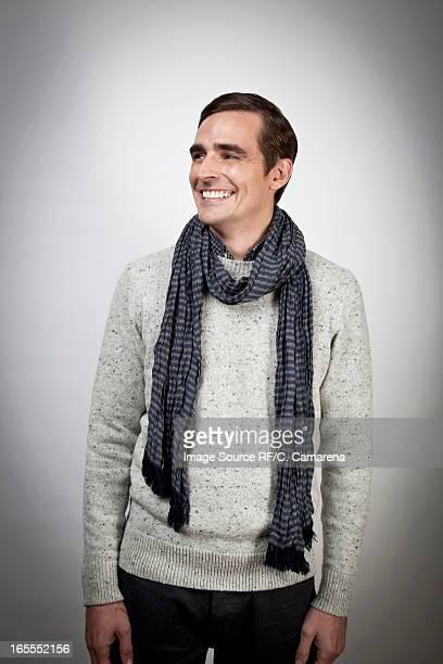 Smiling man wearing scarf indoors