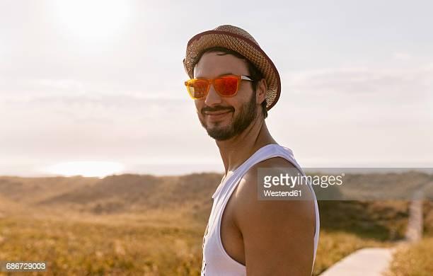 Smiling man wearing straw hat and orange sunglasses