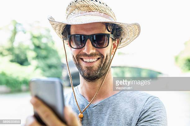 Smiling man wearing straw hat and sunglasses holding cell phone