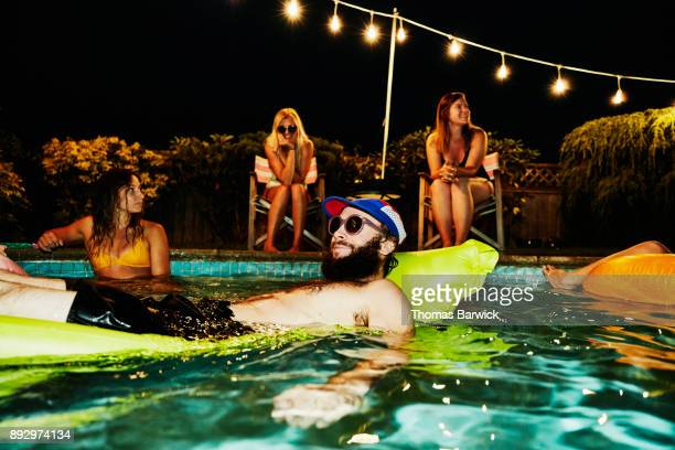 Smiling man wearing sunglasses and floating on air mattress during backyard pool party with friends on summer evening