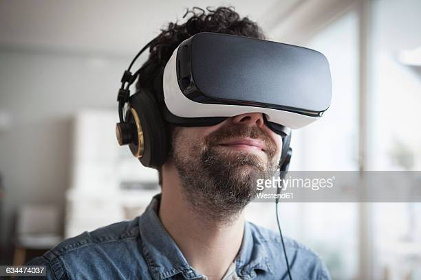 smiling man wearing virtual reality glasses and headphones - virtual reality simulator stock-fotos und bilder