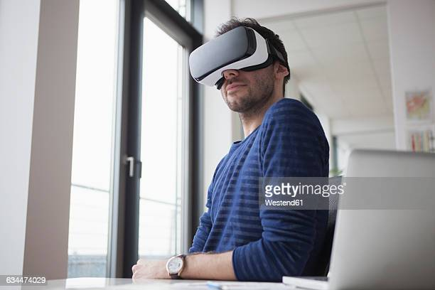 Smiling man wearing Virtual Reality Glasses in the office