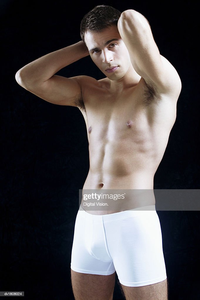 Smiling Man Wearing White Boxer Shorts Stands With His Hands Behind His Head : Stock Photo