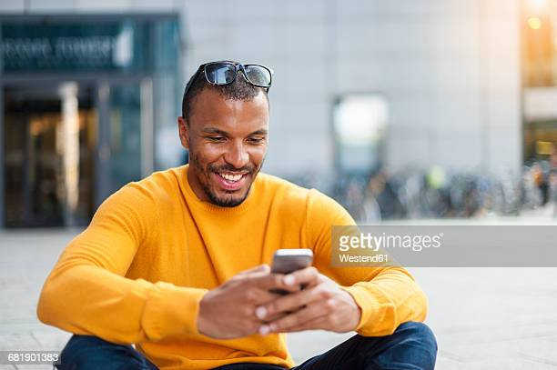 smiling man wearing yellow pullover looking at cell phone - leuchtende farbe stock-fotos und bilder
