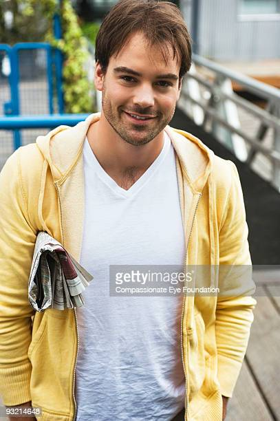 smiling man wearing yellow sweater with newspaper