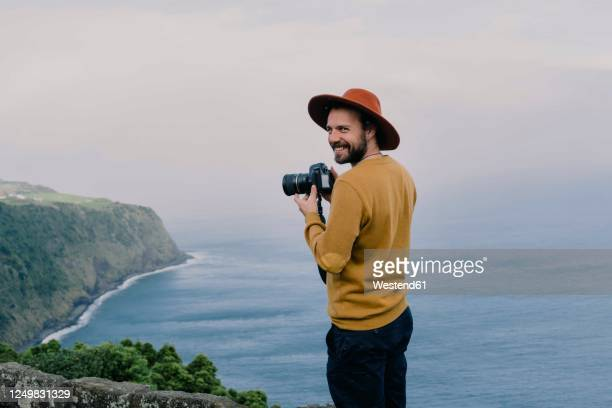 smiling man with a camera at the coast on sao miguel island, azores, portugal - photographer stock pictures, royalty-free photos & images