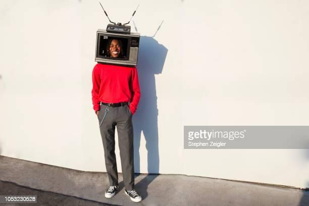 smiling man with a television set on his head - média photos et images de collection