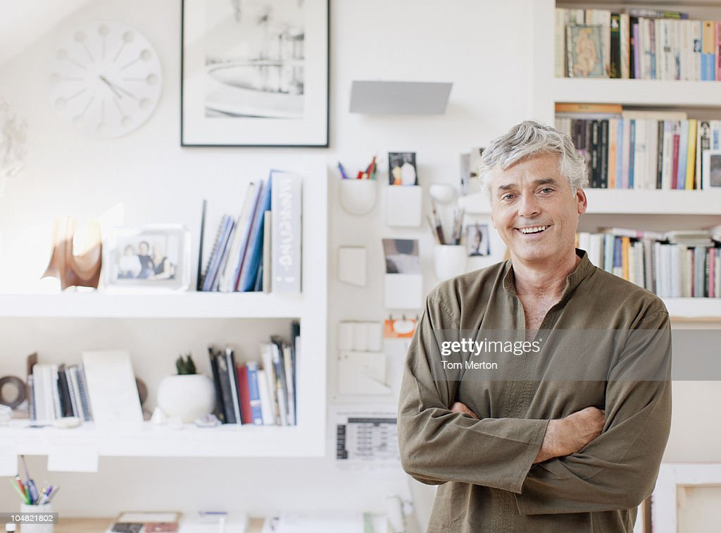 Smiling man with arms crossed in home office : Stock Photo