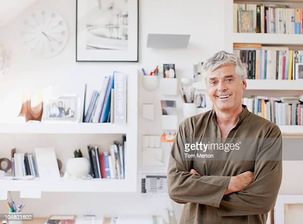 Smiling man with arms crossed in home office
