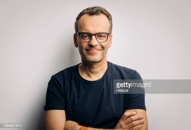 homem sorridente com os braços cruzados usando óculos - acessório ocular - fotografias e filmes do acervo