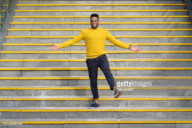 smiling man with arms outstretched standing on staircase - only men stock pictures, royalty-free photos & images