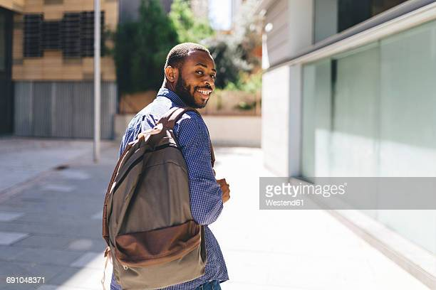 smiling man with backpack - tourner photos et images de collection