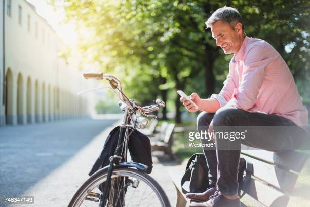 smiling man with bicycle checking the phone on a park bench - tempo libero foto e immagini stock