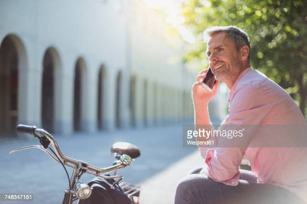 Smiling man with bicycle on the phone on a park bench