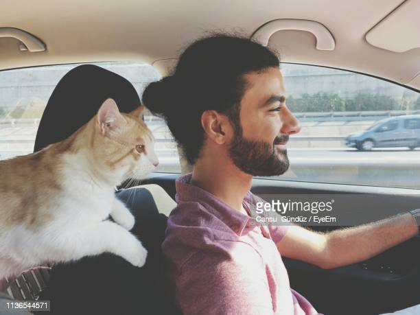 Smiling Man With Cat Sitting In Car