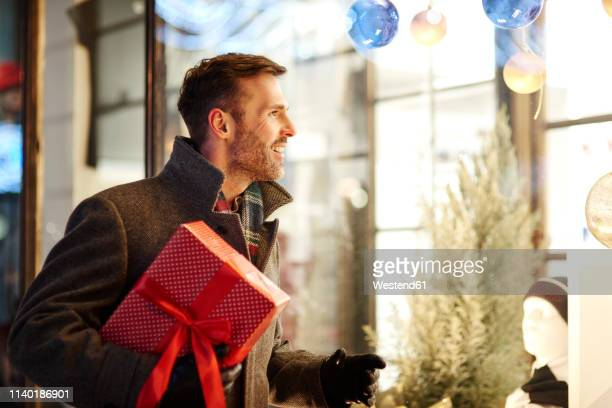 smiling man with christmas present looking in shop window - man shopping stock pictures, royalty-free photos & images
