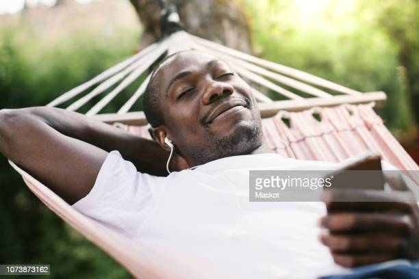smiling man with closed eyes enjoying music through mobile phone while relaxing on hammock - hammock stock pictures, royalty-free photos & images