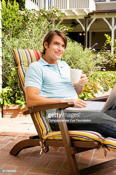 Smiling man with coffee cup and laptop computer
