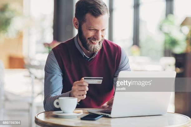 Homme souriant avec carte de crédit et portable au café