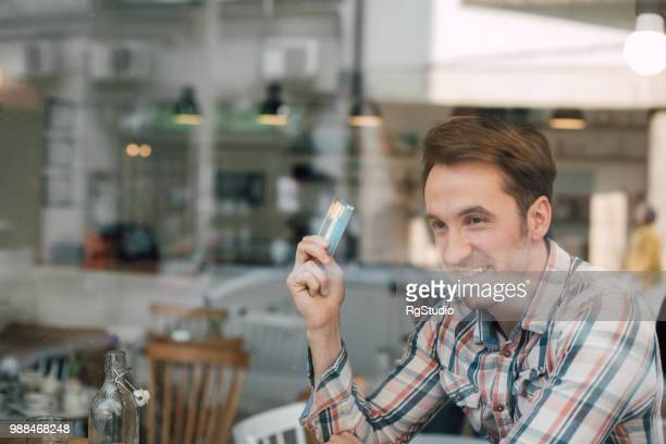 Smiling man with credit card sitting in the coffee shop window