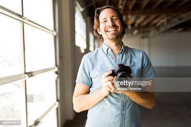 Smiling man with digital camera