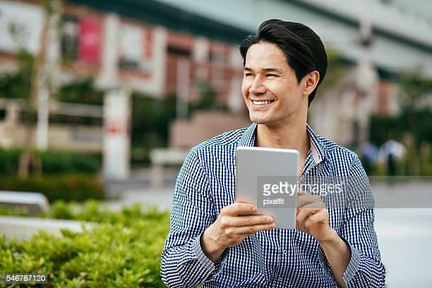 男性、デジタルタブレットを持って笑う