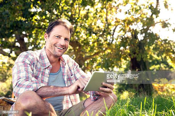 Smiling man with digital tablet sitting on meadow