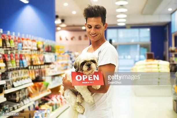 Homme souriant avec chien dans un magasin pour animaux de compagnie