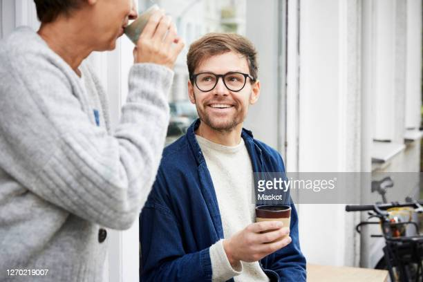 smiling man with female colleague at entrance of art studio - middelste deel stockfoto's en -beelden