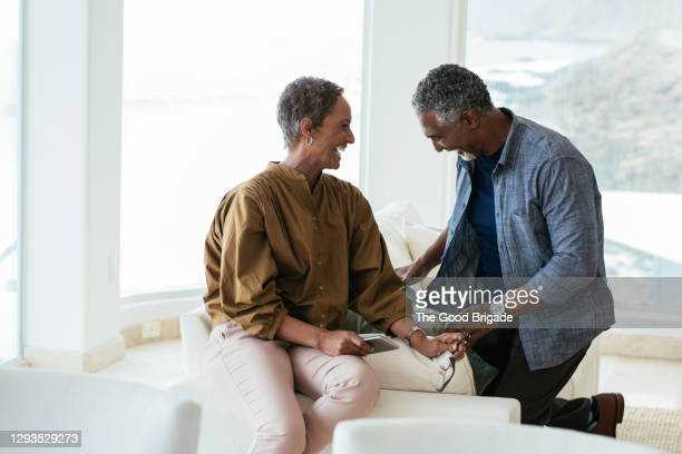smiling man with female partner in living room at home - laughing stock pictures, royalty-free photos & images