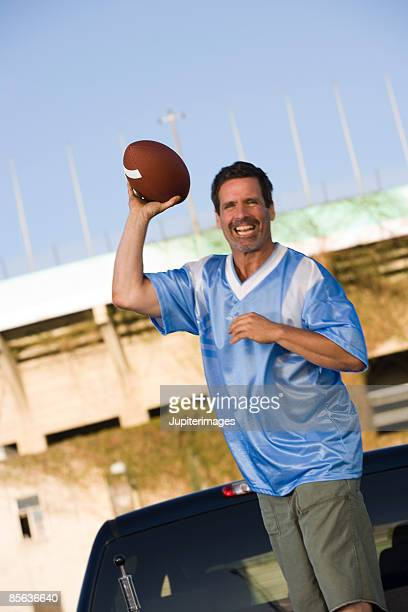 smiling man with football - sports jersey stock pictures, royalty-free photos & images
