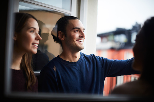 Smiling man with friends looking through window while standing in rental apartment - gettyimageskorea