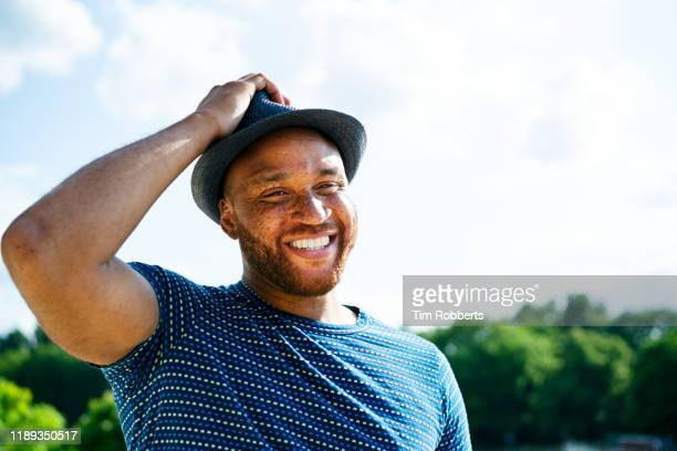 smiling man with hand on hat - chubby stock pictures, royalty-free photos & images