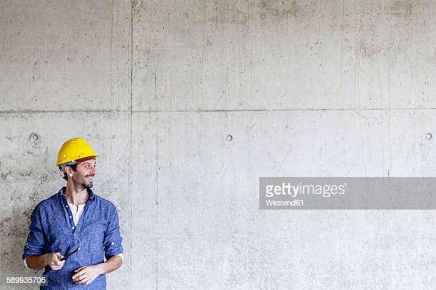 Smiling man with hard hat on construction site at concrete wall