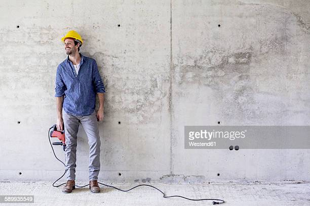 Smiling man with hard hat on construction site holding drill
