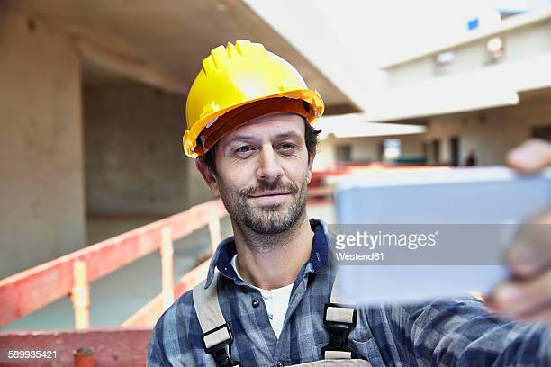 Smiling man with hard hat on construction site taking a selfie
